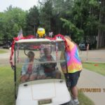 older couple sitting in decorated golf cart