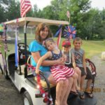 young family sitting on decorated golf cart