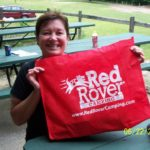 woman showing off red rover camping bag